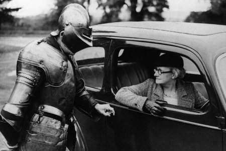 Woman_in_car_being_questioned_by_man_wearing_suit_of_armour